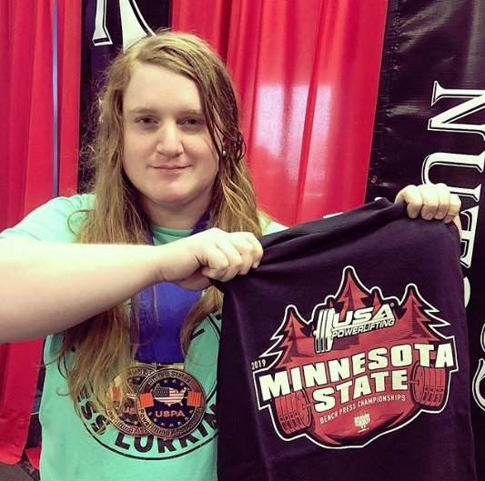 JayCee Cooper holding Minnesota USA Powerlighting Bench Press Championships Shirt